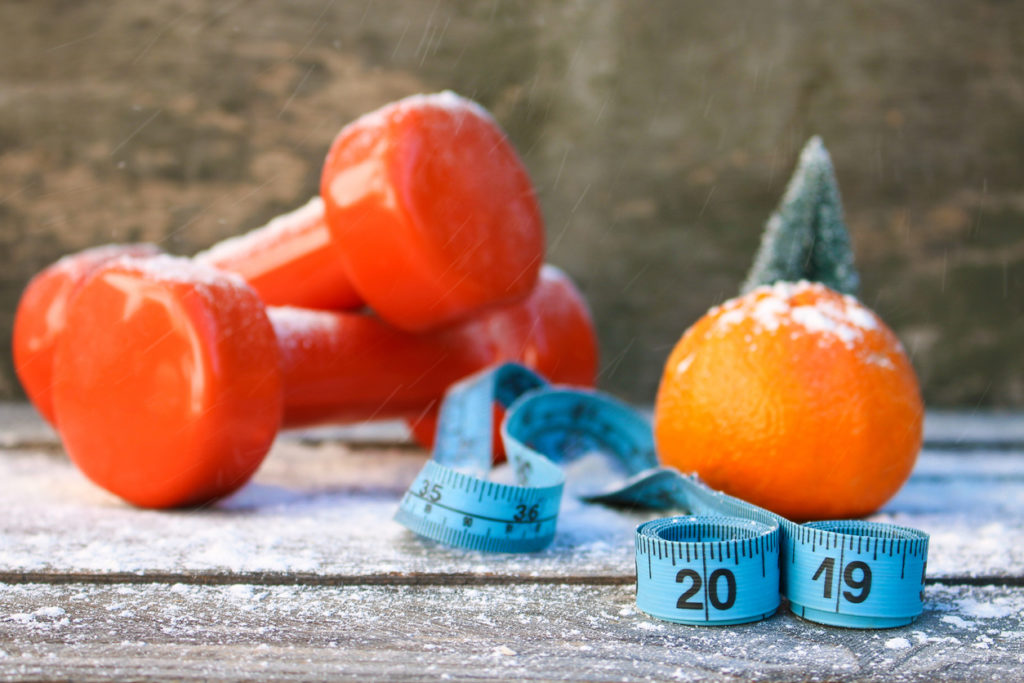 Hand weights, tape measure and fresh orange as reminder to take care of our bodies as we age.