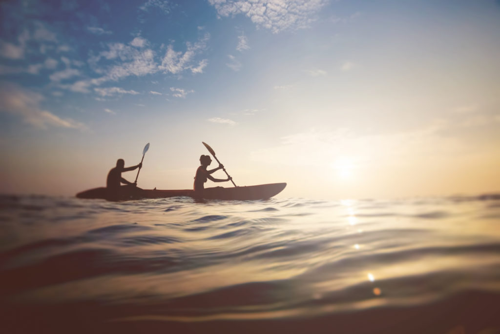 Two people kayaking on ocean with sunset in view.