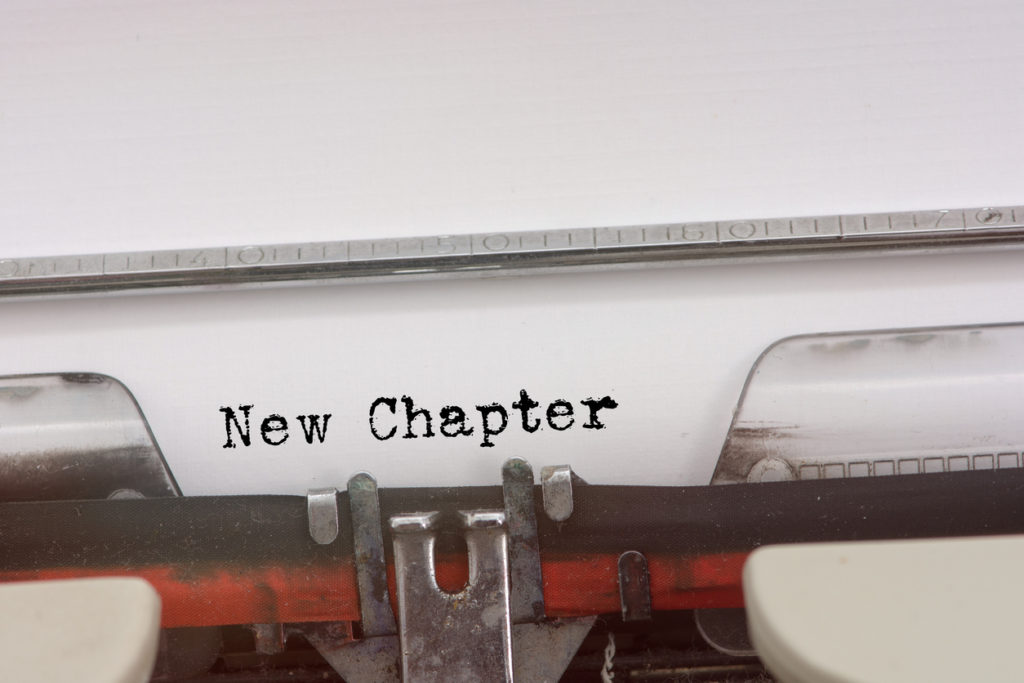 "Vintage typewriter with ""New Chapter"" types out. Reminder for Over 50 women starting a new chapter."